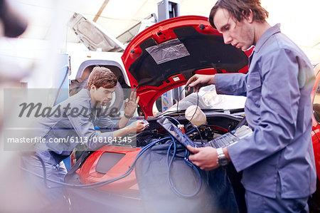 Mechanics working on engine in auto repair shop