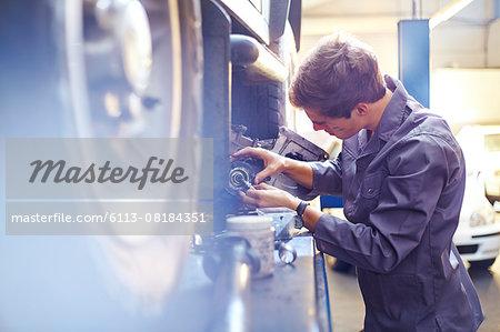Mechanic examining part in auto repair shop