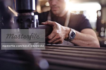 Close up mechanic using machinery in auto repair shop