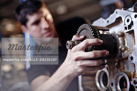 Close up mechanic fixing part in auto repair shop