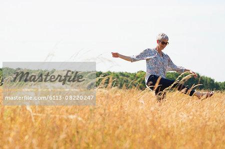 Playful senior woman dancing in sunny rural field
