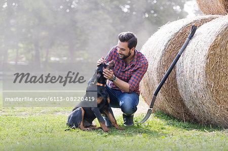 Man petting dog next to rolled hay bales