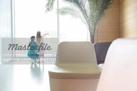 Nurse with pointing girl at hospital lobby window