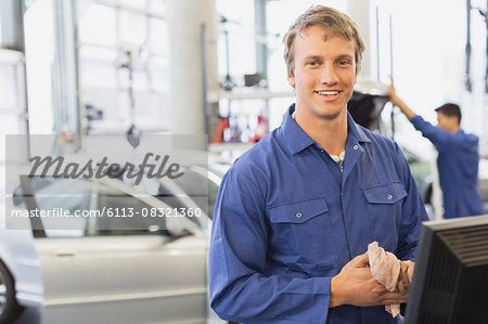 Portrait smiling mechanic at computer in auto repair shop