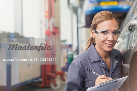 Portrait confident female mechanic with clipboard in auto repair shop