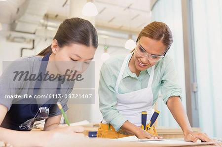 Female carpenters drafting plans in workshop