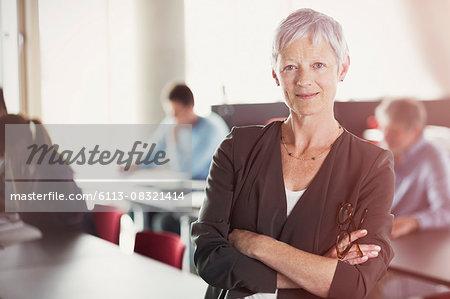 Portrait of confident senior woman in adult education classroom