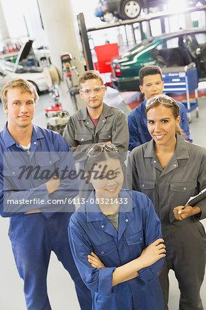 Portrait smiling mechanics in auto repair shop