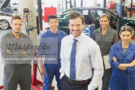 Portrait confident businessman and mechanics in auto repair shop