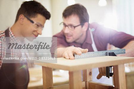Carpenters measuring wood in workshop