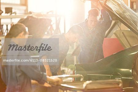 Mechanics looking inside trunk in auto repair shop