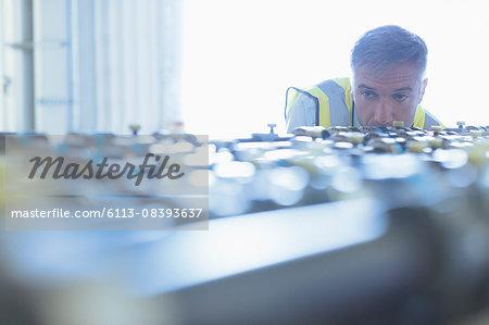 Engineer examining printing press conveyor belt