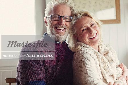 Portrait laughing senior couple hugging