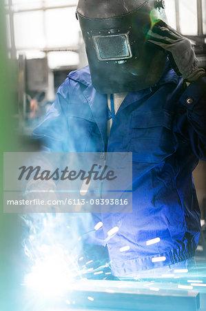 Welder in protective workwear working in factory
