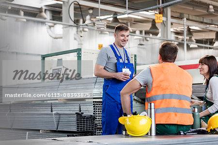 Workers enjoying coffee break in steel factory