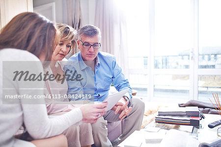 Interior designer using digital tablet in consultation with couple
