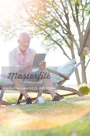 Senior man using digital tablet on lounge chair in backyard