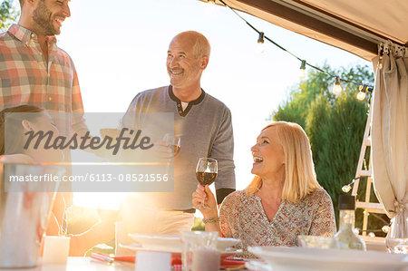 Family drinking wine at sunny patio table
