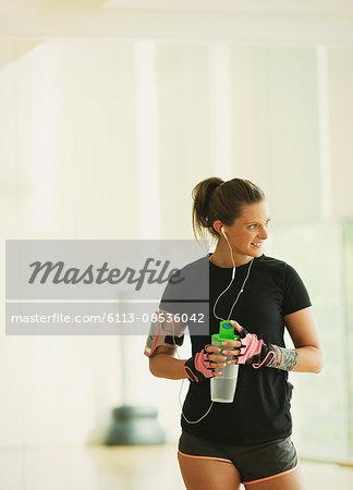 Smiling woman taking a break drinking water in gym studio
