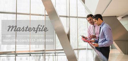 Corporate businessmen using digital tablet at railing in office