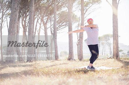 Senior woman practicing yoga in sunny park