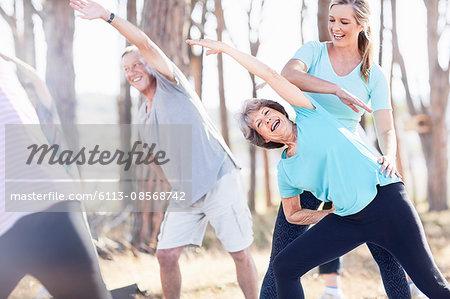 Yoga instructor guiding senior woman in park
