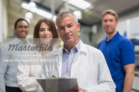 Portrait smiling engineer team in steel factory