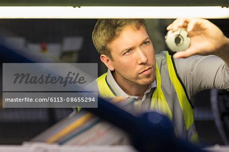 Focused worker inspecting part in steel factory