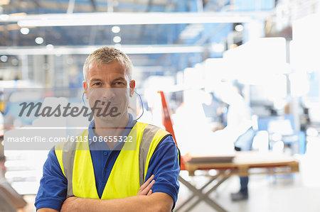 Portrait smiling worker with earplugs in steel factory