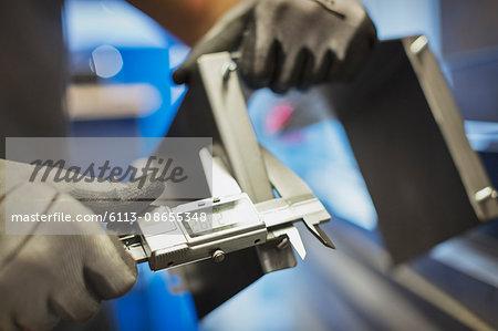 Worker measuring steel with calipers in steel factory