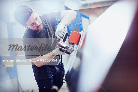 Worker sanding steel in steel factory