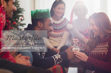Friends watching boyfriend giving Christmas gift to girlfriend
