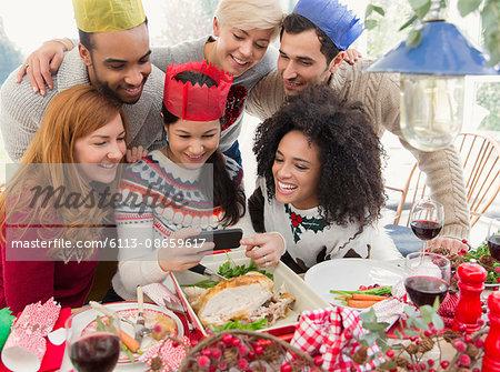Friends wearing paper crowns taking selfie at Christmas dinner