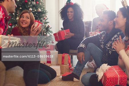 Friends watching playful woman shaking Christmas gift