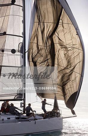 Man adjusting sail on sailboat