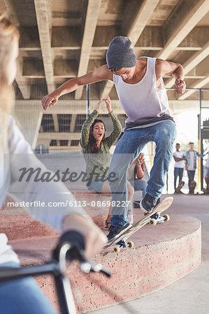 Friends watching teenage boy skateboarding at skate park