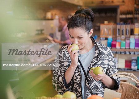 Woman smelling pears in market