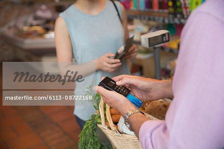 Grocery store clerk using credit card machine
