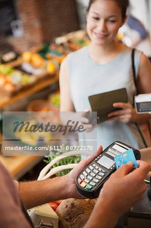 Woman watching grocery store clerk using credit card machine