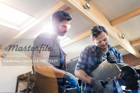 Metal workers using sander in workshop
