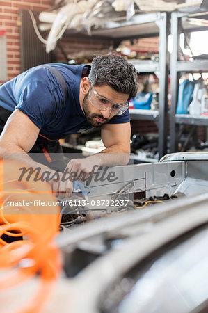 Focused mechanic fixing car in auto repair shop