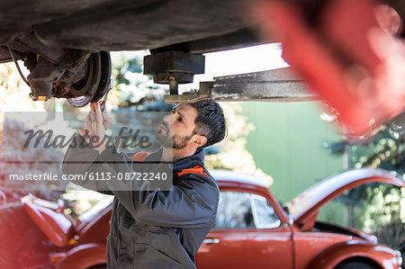 Mechanic underneath car fixing brakes