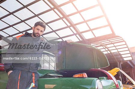Portrait confident mechanic fixing classic car in auto repair shop
