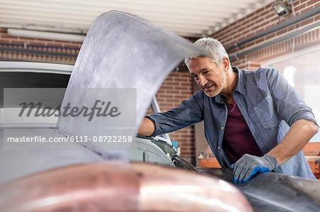 Mechanic looking under automobile hood in auto repair shop
