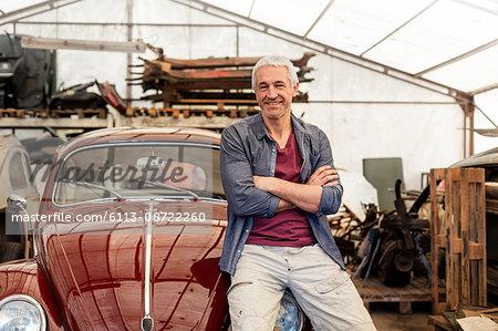 Portrait confident mechanic leaning on classic car in auto repair shop