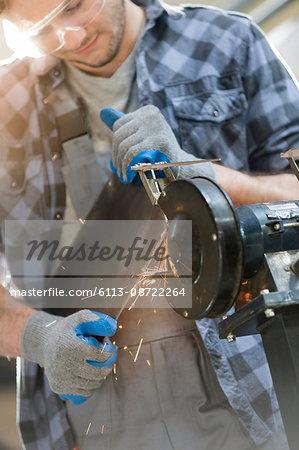 Metal worker using sander in workshop