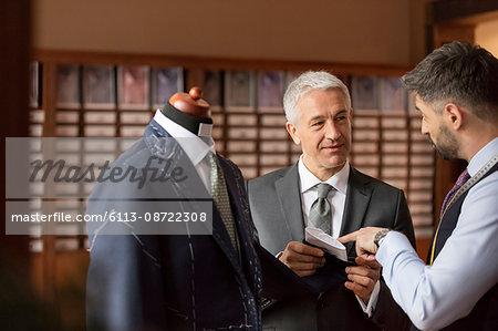 Tailor explaining suit to businessman in menswear shop