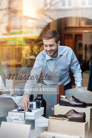 Worker arranging window display in menswear shop