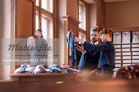 Worker showing ties to businessman in menswear shop