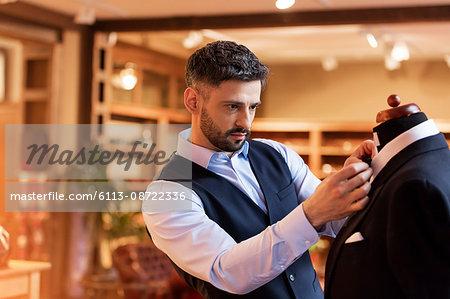 Tailor adjusting tie on dressmakers model in menswear shop